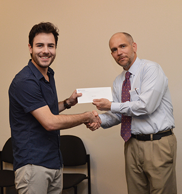 Mario Balcazar, left, a graduating senior with degrees in electrical engineering and physics, is congratulated by Professor and Director of University Honors Program Bryan Young. Balcazar is recipient of KU's 2018 Phi Kappa Phi Blackiston Fellowship.